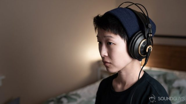 A photo of the AKG K240 Studio semi-open headphones being worn by a woman angled slightly away from the camera.