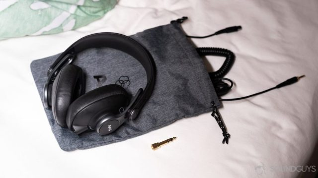A picture of the AKG K371 wired over-ear headphones on the included drawstring carrying pouch with the included cables.