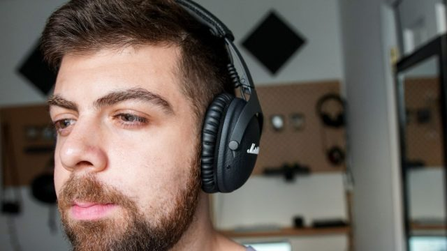 Man wearing Marshall Monitor II ANC headphones with desk in background