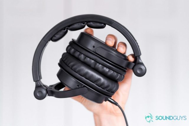 Best headphones under $200: The Monoprice 8323 over-ear headphones being raised in a hand. White background.