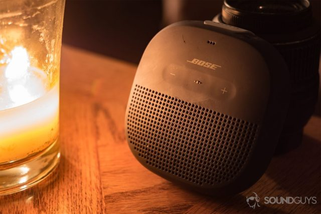 The Bose SoundLink Micro (blue) next to a large candle on a wood tabletop.