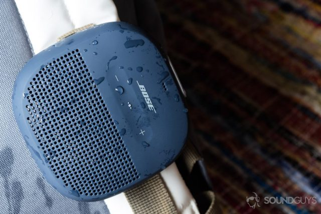 The Bose SoundLink Micro (blue) hooked onto a white backpack.