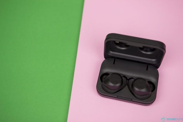 Shot of the open charging case with the Elite Sport true wireless earbuds charging inside against a pink board.