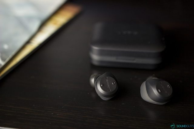 The Jabra Elite Sport earbuds on a black counter with the charging case in the background.