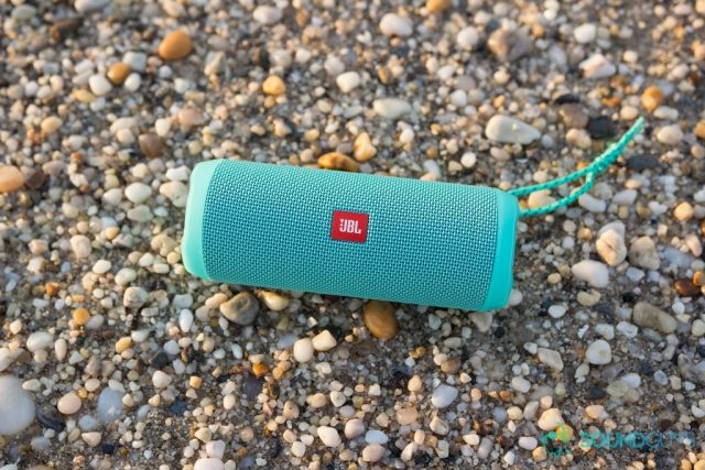 The teal JBL Flip 4 pictured on a rocky beach.