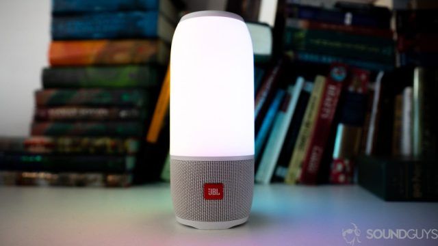 The JBL Pulse 3 in front of a books on a white desk.