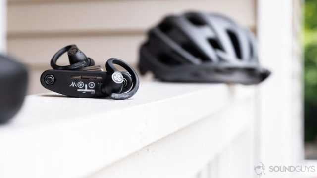 The earbuds resting on a bike tool with a bike helmet in the background.