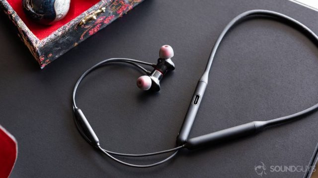 OnePlus Bullets Wireless 2: Full image of the earbuds and neckband with the cable curling up and around on a black table.