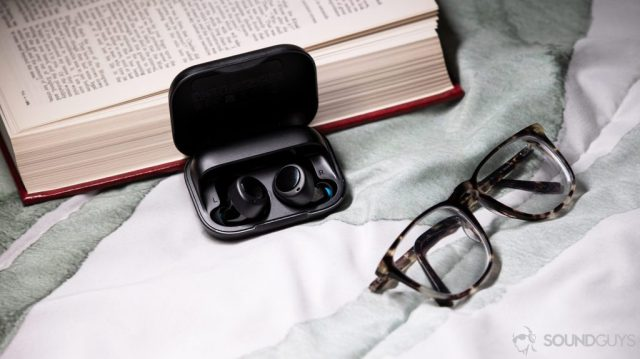 A picture of the Amazon Echo Buds in the case next to glasses and a book.