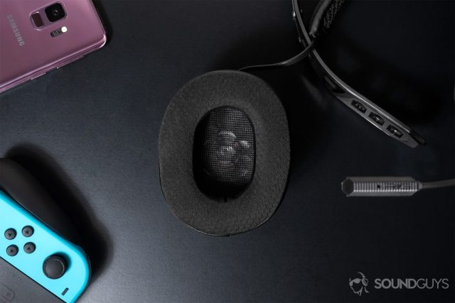 Top-down image of the detachable ear cup, both are detachable, with a Nintendo Switch in the bottom left corner and a Samsug S9 (lilac) in the top left corner of the image.