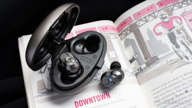 A photo of the HiFiMan TWS600 true wireless earbuds with one earbud in and the other out of the oblong open charging case on top of a book.