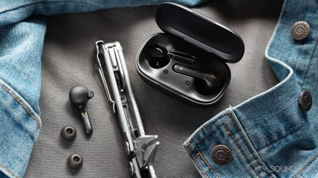 A picture of the Anker Soundcore Life P2 true wireless earbuds, ear tips, and case next to a Leatherman multitool and denim jacket.