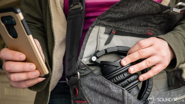 A photo of a man shoving the Audio-Technica ATH-M50xBT into a bag.