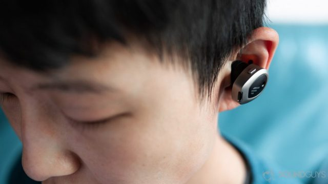 A picture of the Edifier TWS NB true wireless noise cancelling earbuds worn by a woman looking down to show how much they protrude from the ear.