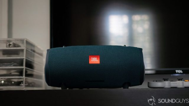 Shot of the JBL Xtreme 2 from the front on top of a black table with a TV in the background.