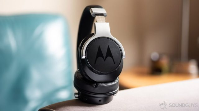 A photo of the Motorola Escape 500 ANC noise cancelling headphones propped up on a grey cloth surface.