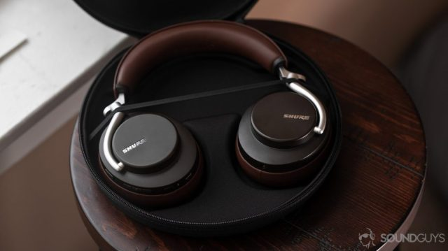 An aerial photo of the Shure Aonic 50-noise cancelling headphones open carrying case revealing the headphones in brown.