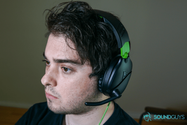 A man wears The Turtle Beach Recon 70 gaming headset sitting at a PC