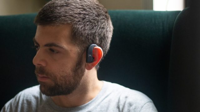 A picture of a man sitting on green chair wearing the Anker Soundcore Spirit X2 true wireless earbuds.