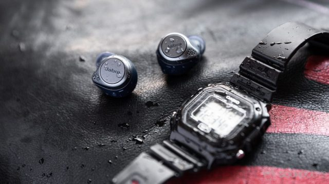 A picture of the Jabra Elite Active 75t true wireless workout earbuds (navy) covered in water droplets behind a Casio digital watch.