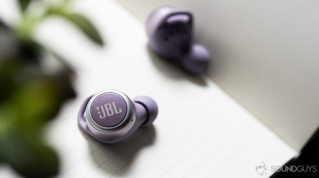 A picture of the JBL LIVE 300 TWS true wireless earbuds on a notebook.