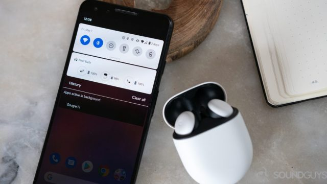 The new white Google Pixel Buds on a marble table next to Pixel 3 with battery card displayed