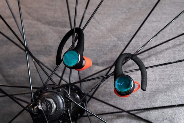 A picture of the Plantronics BackBeat Fit 3100 earbuds hanging from the spokes of a road bike wheel.