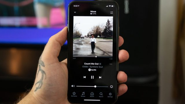 Man holding iPhone 11 Pro with music playing in the Sonos app