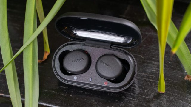Sony WF-XB700 earbuds in the charging case with the lid open on a black table with plants in the foreground