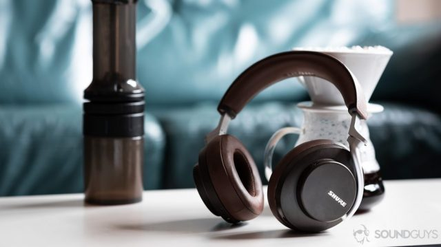 A picture of the Shure Aonic 50 noise cancelling Bluetooth headphones in brown leaning against a coffee carafe.