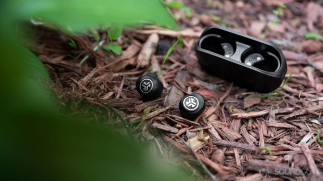 A photo of the JLab GO Air cheap true wireless earbuds with the earbuds outside of the case on a mulch pile, almost obscured by leaves in the foreground.
