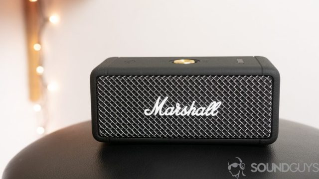 Marshall Emberton Bluetooth speaker on a black stool with lights in the background