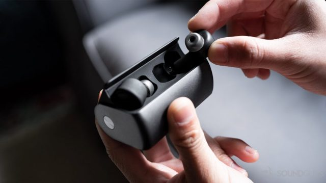 A picture of the RHA TrueConnect 2 case being held in a woman's hand as the other hand removes the far earbud.