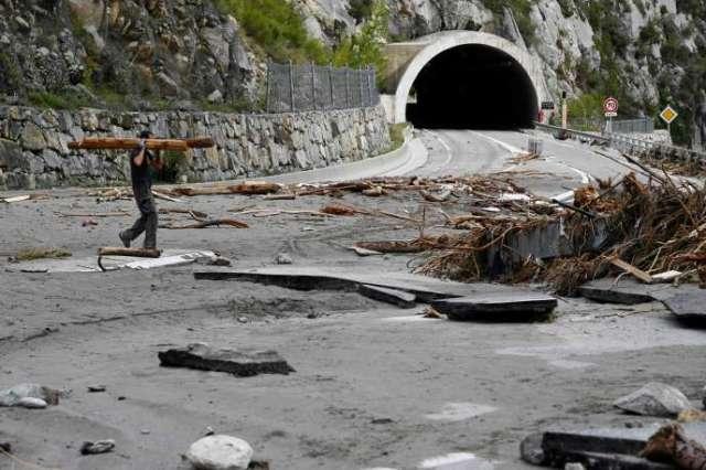 Un homme transporte du bois, le 6 octobre 2020, sur la route endommagée menant à Breil-sur-Roya, village ravagé par les inondations, dans les Alpes-Maritimes.