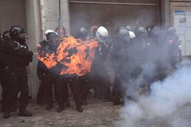 Des membres de la brigade française de répression des actions violentes (BRAV) sont encerclés par un feu, lors d'une manifestation pour les «droits sociaux» et contre le projet de loi «sécurité globale», dont l'article 24 criminaliserait la publication d'images de policiers en service, à Paris, le 5 décembre.
