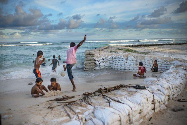 kids playing near sand bags