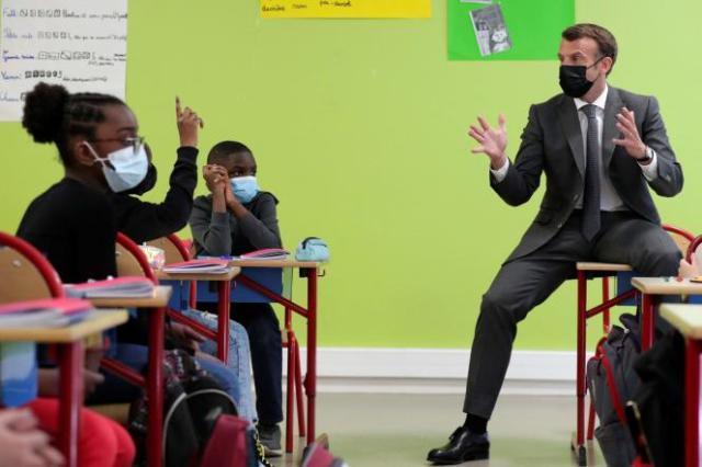 Emmanuel Macron échange avec élèves lors d'une visite dans une école primaire de Melun (Seine-et-Marne), le 26 avril.