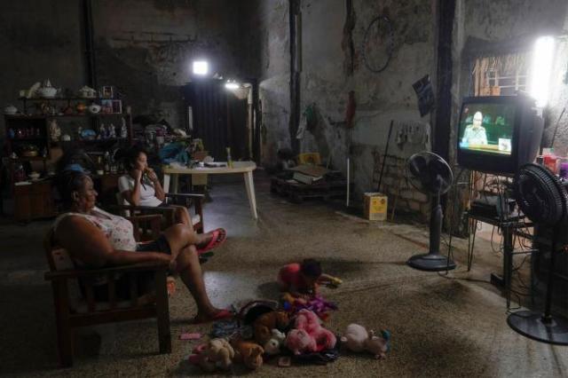 Une famille regarde Raul Castro lors de la session d'ouverture du 8e congrès du Parti communiste de Cuba, le 16 avril.