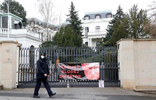 Un policier tchèque devant l'ambassade de Russie à Prague, vendredi 16 avril. Sur la grille d'entrée, une banderole représentant Vladimir Poutine avec les inscription« tueur, voleur, dictateur».