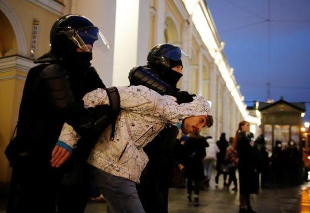 Un manifestant est emmené par des agents des forces de l'ordre, à Saint-Pétersbourg, en Russie, le 21 avril.