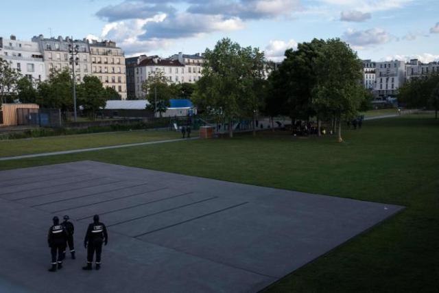 Des policiers municipaux patrouillent le 19 mai 2021 dans les jardins d'Eole à Paris, fermé depuis plusieurs jours au public pour servir de lieu d'accueil aux personnnes addictes au crack, et les éloigner des espaces publics autour de la place Stalingrad.