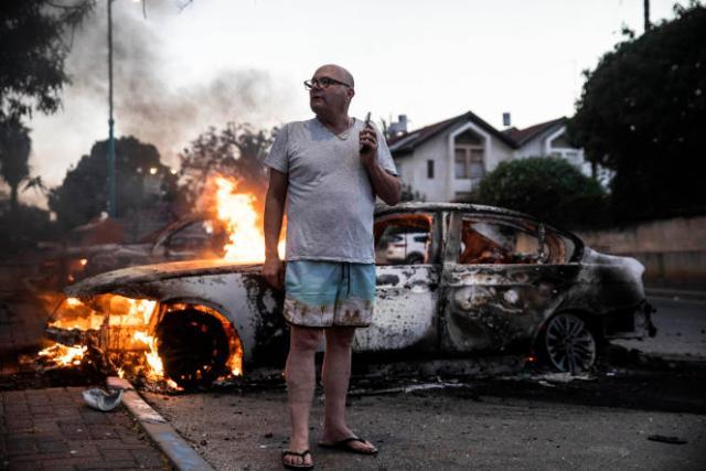 Un passant devant une voiture incendiée pendant des émeutes survenues à Lod dans la banlieue de Tel-Aviv, le 11 mai 2021.