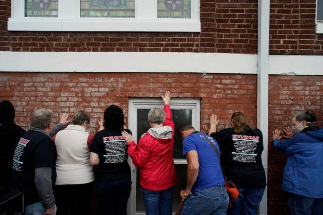 Des gens prient, la main sur un mur de l'égliseépiscopaleméthodisteafricaine historique deVernon, à Tulsa (Oklahoma), le 31 mai 2021.