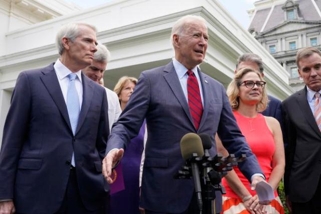 Le président Joe Biden, entouré de sénateurs des deux bords, devant la Maison Blanche, avant leur rencontre pour discuter d'un plan d'infrastructures, le 24 juin 2021.