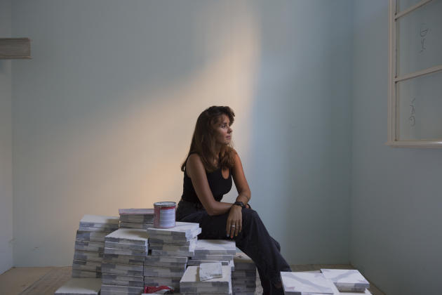 L'architecte Lea Ghorayeb, sur une pile de carrelage dans la chocolaterie que l'ONG Baytna Baytak, où elle travaille, est en train de reconstruire à Mar Mikhaël, à Beyrouth, le 1er août 2021.