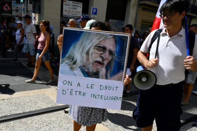 Une manifestante brandit une photo de Didier Raoult à Marseille, samedi 21 août 2021.