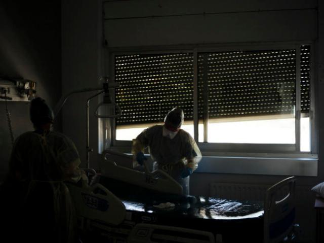 Une aide-soignante nettoie une chambre après le décès d'un patient dans le service Covid-19 du Centre hospitalier de Bastia, le 16 août 2021.