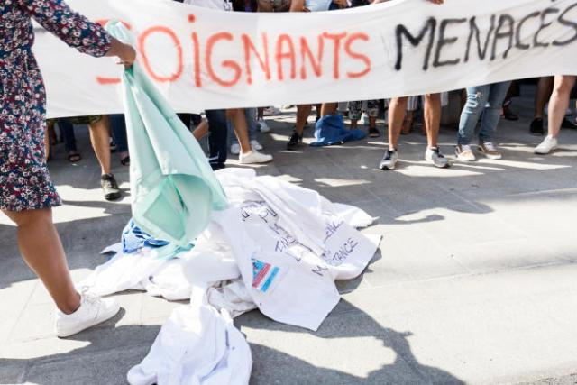Les soignants du collectif ajaccien Soignants Menacs déposent symboliquement leur blouse devant la Préfecture de Corse-du-Sud sur le Cours Napoléon à Ajaccio, afin de manifester leur opposition à la vaccination obligatoire, le 11 septembre 2021.