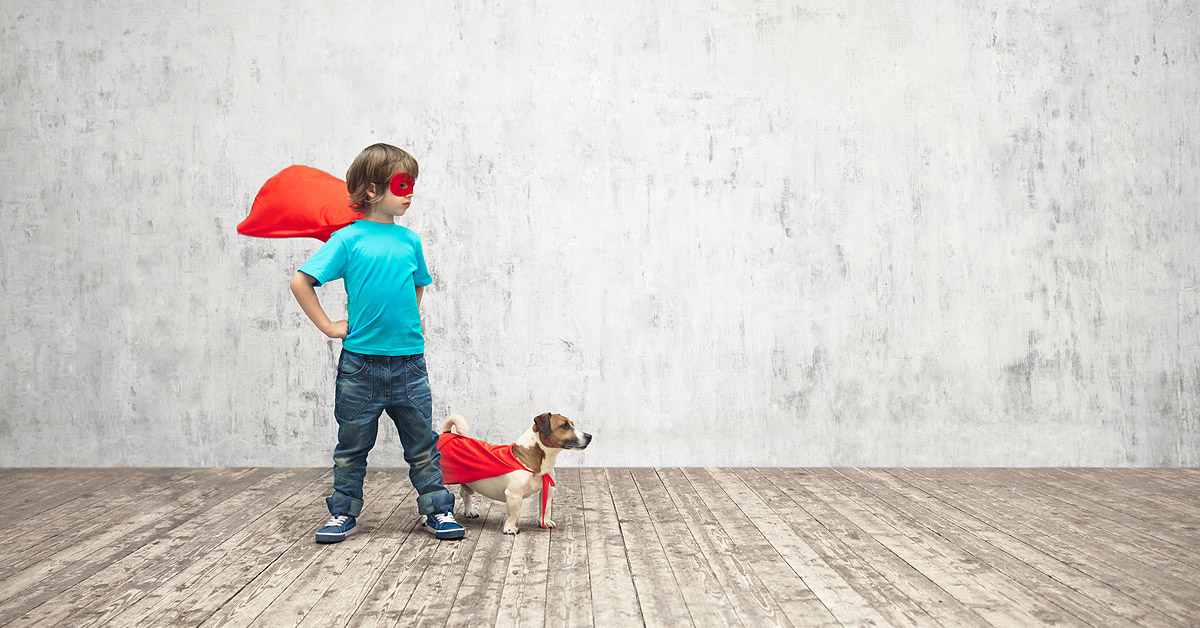 A young boy and his jack russell puppy stand side by side looking stage right. They are both wearing red caps that are flying behind them. The boy is also wearing a red mask. All to help promote the https://www.ultimatepuppy.com/2018/03/count-down-to-puppy-part-1-of-3/ series