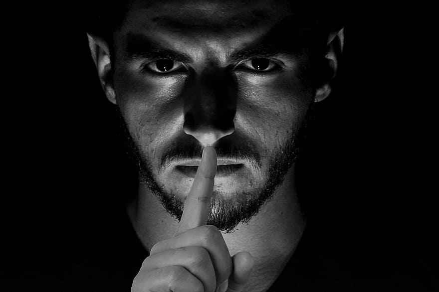 Una morte silenziosa: un uomo dallo sguardo serio con il dito indice davanti alla bocca.